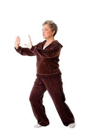 Beautiful Senior woman doing Tai Chi exercise to keep her joints flexible, isolated.