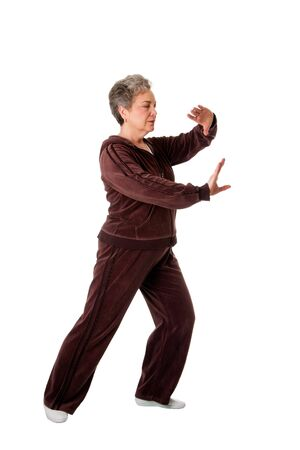 tai chi: Beautiful Senior woman doing Tai Chi exercise to keep her joints flexible, isolated.