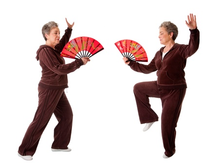 Beautiful Senior woman doing Tai Chi exercise with red dragon fan to keep her joints flexible, isolated. Фото со стока