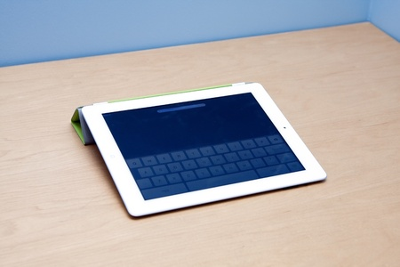 The new iPad 2 from Mac Apple, on a wooden desk and blue background with visible keypad touchscreen and forward facing camera. Editorial