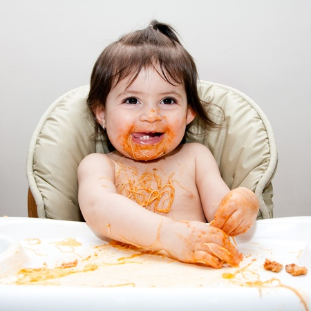 messy: Happy baby having fun eating messy covered in Spaghetti Angel Hair Pasta red marinara tomato sauce.
