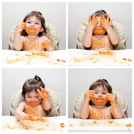 Happy baby having fun eating messy showing hands covered in Spaghetti Angel Hair Pasta red marinara tomato sauce.