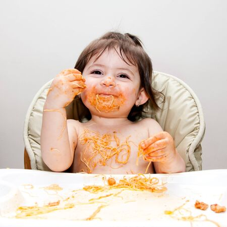 Happy smiling baby having fun eating messy covered in Spaghetti Angel Hair Pasta red marinara tomato sauce. Archivio Fotografico