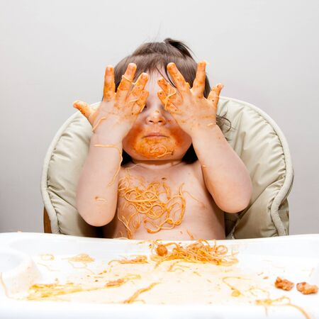Happy baby having fun eating messy showing hands covered in Spaghetti Angel Hair Pasta red marinara tomato sauce. Stock Photo - 9234122