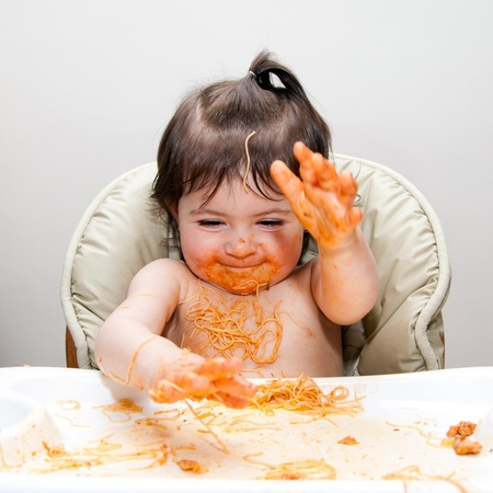 Happy baby having fun eating messy slapping hands covered in Spaghetti Angel Hair Pasta red marinara tomato sauce. Stockfoto