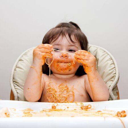 Happy baby having fun eating messy covered in Spaghetti holding Angel Hair Pasta red marinara tomato sauce.