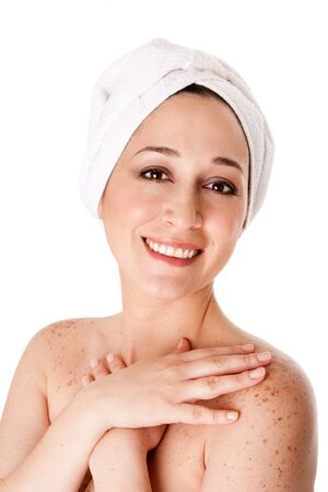 Beautiful happy healthy radiant woman female face with towel around head finished bath shower spa treatment touching her shoulder skin with freckles, isolated. photo