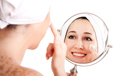 Beautiful happy smiling woman face applying exfoliating cream as anti-aging skincare treatment while looking at mirror, isolated.