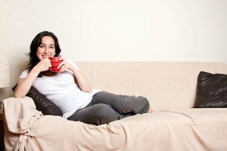 laid back: Beautiful happy young woman sitting relaxed laid back on sofa couch in livingroom drinking a beverage.
