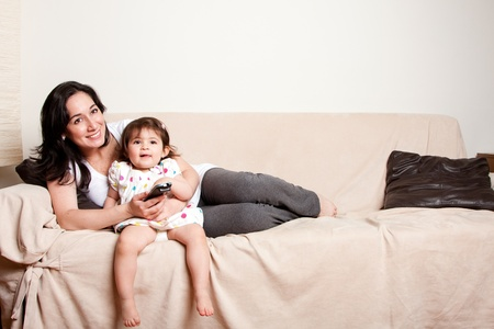 Beautiful happy family mother and baby toddler daughter sitting relaxed laid back on sofa couch in livingroom watching TV television.