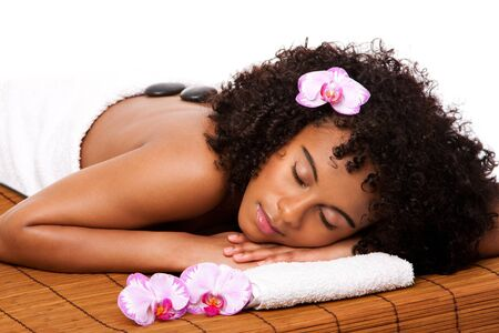 Beautiful happy relaxed Latina-African woman at health day spa with hot stone massage treatment laying in white towel on bamboo table decorated with orchids.