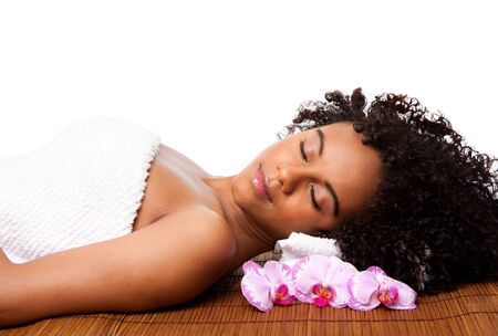 massage: Beautiful happy peaceful sleeping woman at a day spa, laying on bamboo massage table with head on pillow wearing a towel and orchid flowers around, isolated. Stock Photo