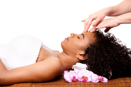 Beautiful happy peaceful sleeping woman at day spa, laying on bamboo massage table with head on pillow wearing a towel getting a facial massage, isolated. Stock Photo - 9577515