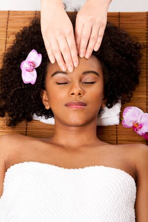 Beautiful happy peaceful sleeping woman at day spa, laying on bamboo massage table with head on pillow wearing a towel getting a facial massage.