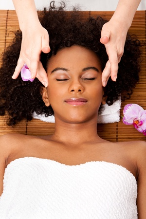 facial: Beautiful happy peaceful sleeping woman at day spa, laying on bamboo table with head on pillow wearing a towel getting a facial temple massage, isolated. Stock Photo