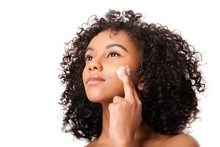 Mooie jonge Braziliaanse vrouw die masseert exfoliërende anti-aging crème gezichtsmasker - huidverzorging cosmetologie - geïsoleerd. Stockfoto