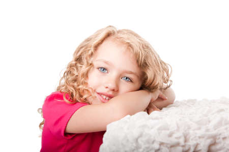 Beautiful cute happy smiling girl with blue eyes daydreaming laying on soft surface, isolated.