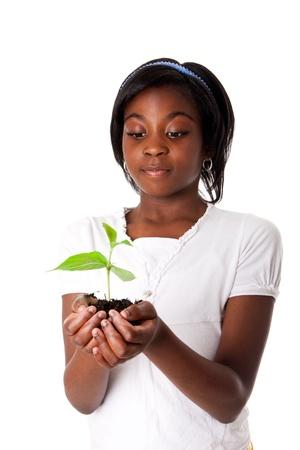 分離された美しいアフリカの女の子の手の手のひらから成長している若い新工場。地球の概念の干ばつ。