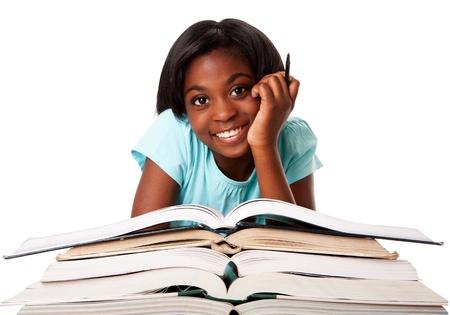 ni�os negros: Hermosa estudiante sonriente feliz con pluma y una pila de libros abiertos haciendo deberes, aislado.