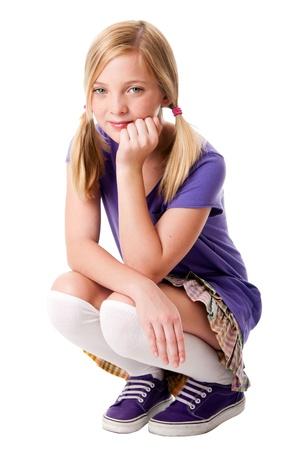 squatting: Hermosa adolescente feliz sentado okupado llevando calcetines de rodilla, puple deportivo zapatos, camiseta y falda colorida, mano apoyando su cabeza, aislados.