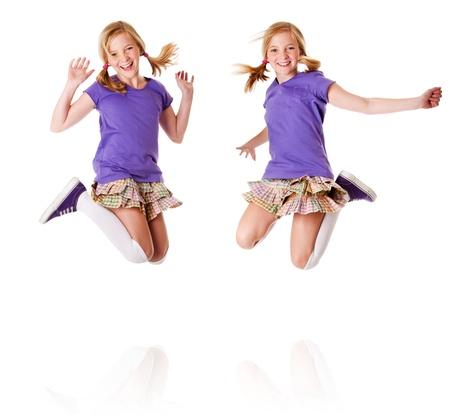 Gelukkig tiener meisjes identieke tweelingen springen en te lachen van geluk plezier, geïsoleerd.