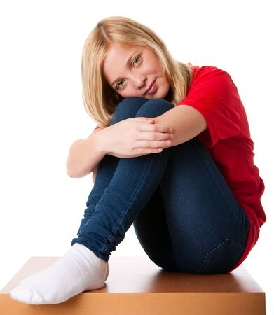 knees up: Cute teenager girl feeling lonely sitting alone with knees pulled up and arms around legs, isolated. Stock Photo