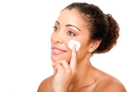 Beautiful face of young woman with hand applying exfoliating anti wrinkle cream beauty treatment for skincare, isolated.