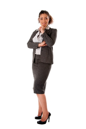 business woman standing: Beautiful self confident curly brunette corporate business woman standing with hand on chin and smiling wearing skirt blouse and black pumps, isolated. Stock Photo