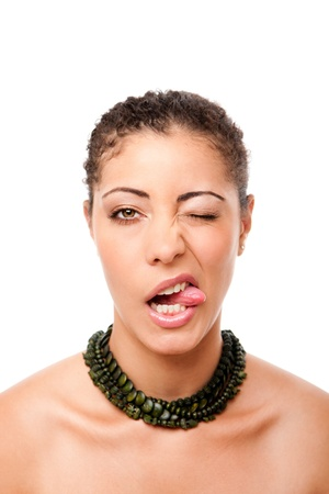 mouth closed: Funny face of a beautiful attractive fashion model sticking out tongue while winking, wearing green necklace, isolated.