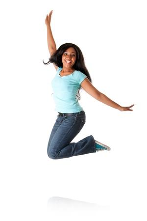 Mooie gelukkige glimlachende Afrikaanse Caribbean tiener springen van geluk te vieren, die blauw overhemd en jeans, geïsoleerd. Stockfoto