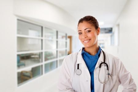 Mooie aantrekkelijke gelukkig lachend vrouwelijke arts arts verpleegster permanent in ziekenhuis gang hall manier voor patiënten consultancy gebied wachtkamer.