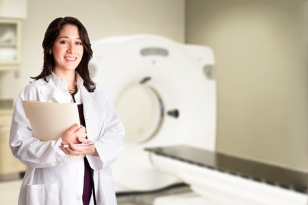 Beautiful happy female doctor physician radiologist holding patient medical chart and pen standing in CT CAT Scan room at hospital, isolated. photo