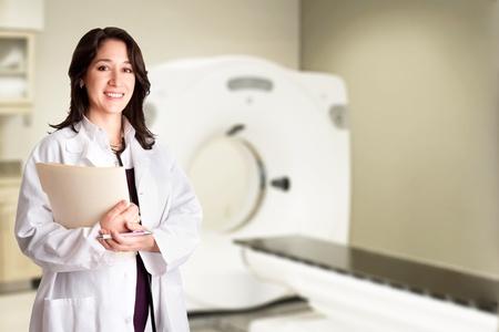 Mooie vrolijke vrouwelijke arts arts radioloog holding patiënt medische kaart en pen staan in CT-CAT-scan kamer in het ziekenhuis, geïsoleerd. Stockfoto