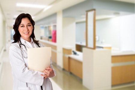 nurses station: Attractive female doctor with white coat and stethoscope standing holding a patient file chart dossier in corridor hallway at hospital clinic with nursestation desk. Stock Photo