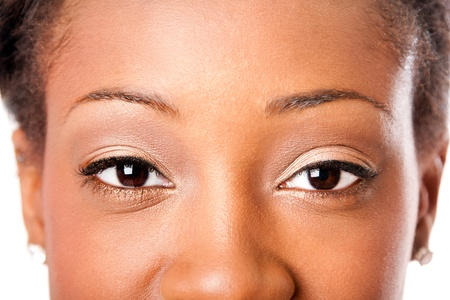 Beautiful almond shaped eyes with natural makeup cosmetics of an African young attractive woman, looking at camera.