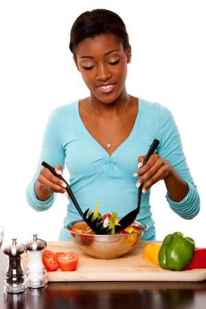 Mooie gezondheidsbewuste jonge vrouw gooien gezonde biologische salade in de keuken, geïsoleerd. Stockfoto