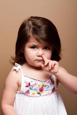 Linda chica niño travieso con el dedo en la nariz de la pesca de mocos mocos, en marrón. Foto de archivo