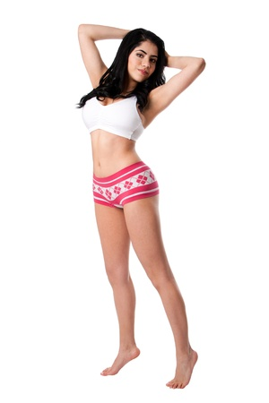 tiptoe: Beautiful in shape healthy happy young woman standing tiptoe stretching wearing white underwear shirt and pink hotpants, isolated.
