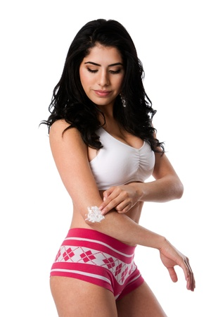 Beautiful young woman applying exfoliating moisturizing cream on dry elbow skin, isolated. Imagens