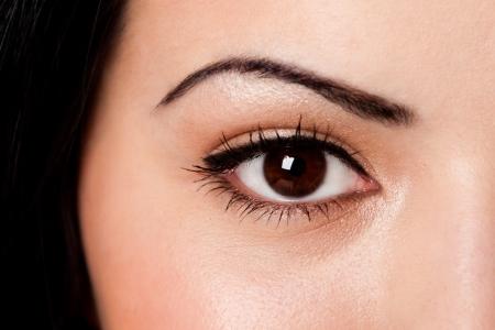 Schöne weibliche Augenbraue und braune Augen mit Wimpern auf heller Haut.