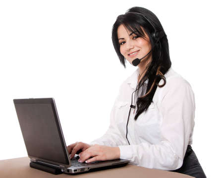 Beautiful happy customer service representative at call center office desk with headset and laptop computer online chatting, isolated. Stock Photo - 12611551