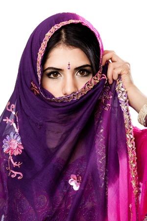 Hermosa mujer bengalí hindú en el colorido vestido de celebración velo delante de la cara, aislado