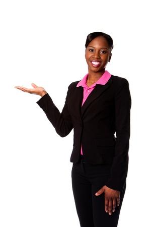 Mooie gelukkig lachende Afrikaanse corporate business student vrouw in pak staan de presentatie van producten met de hand, geïsoleerd.