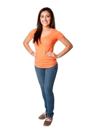 Mooie gelukkig lachende vertrouwen tiener jonge vrouw die zich met de handen op de heup dragen van oranje shirt en blauwe spijkerbroek, geïsoleerd.
