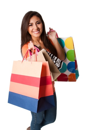 Beautiful Happy smiling young woman on shopping spree carrying colorful bags with merchandise, isolated. Stock Photo