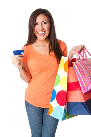 Beautiful Happy smiling young woman on shopping spree with credit card lastic money carrying colorful bags with merchandise presents, isolated. Stock Photo