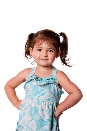 Schattig klein jonge peuter meisje met houding grijns, handen op de heupen en staartjes in het haar, geïsoleerd. Stockfoto