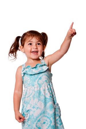 Cute little toddler girl pointing up wearing blue dress and pigtails in hair, isolated.