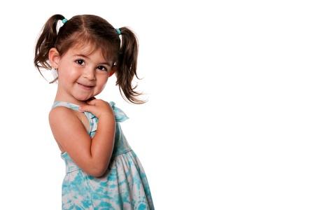 Mooie Cute peuter meisje met staartjes wijzend naar zichzelf in blauwe zomer jurk, geïsoleerd. Wie, ik expressie.