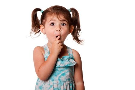 Cute surprised little toddler girl with finger in front of mouth making silence shhh gesture, isolated. Archivio Fotografico
